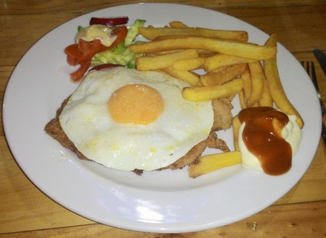 Pork schnitzel with pineapple, fried egg, french fries and salad