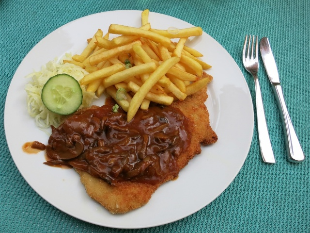 Pork schnitzel with mushroom sauce, french fries and salad